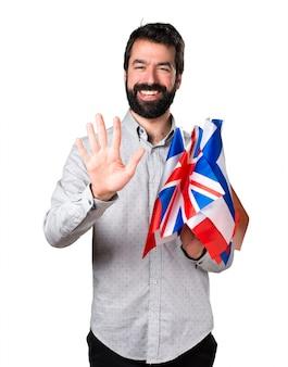 Hermoso hombre con barba sosteniendo muchas banderas y cinco