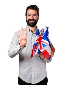 Hermoso hombre con barba sosteniendo muchas banderas y contando cuatro