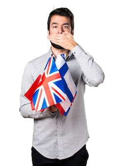 Hermoso hombre con barba sosteniendo muchas banderas y cubriendo su boca