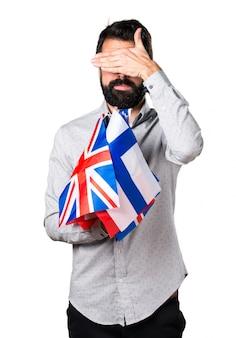 Hermoso hombre con barba sosteniendo muchas banderas y cubriendo sus ojos