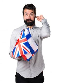 Hermoso hombre con barba sosteniendo muchas banderas y cubriendo sus orejas