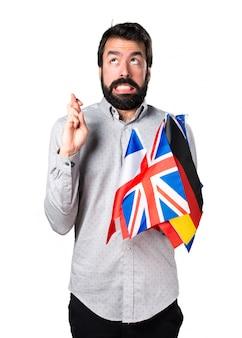 Hermoso hombre con barba sosteniendo muchas banderas y con los dedos cruzando