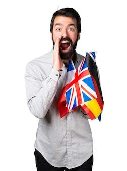 Hermoso hombre con barba sosteniendo muchas banderas y gritando