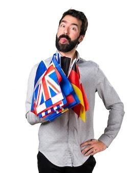 Hermoso hombre con barba sosteniendo muchas banderas y haciendo una broma