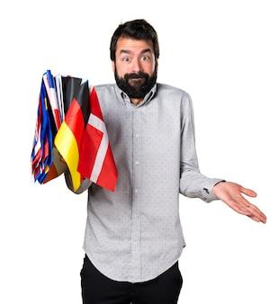 Hermoso hombre con barba sosteniendo muchas banderas y haciendo gesto sin importancia