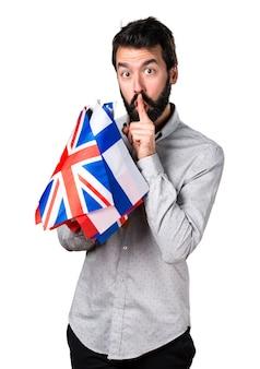 Hermoso hombre con barba sosteniendo muchas banderas y haciendo gesto de silencio