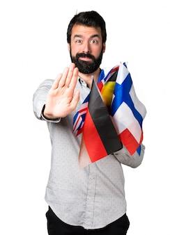 Hermoso hombre con barba sosteniendo muchas banderas y haciendo señal de stop