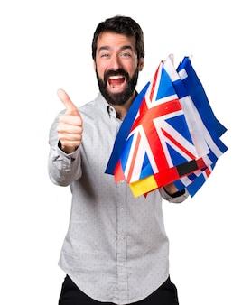 Hermoso hombre con barba sosteniendo muchas banderas y con el pulgar hacia arriba