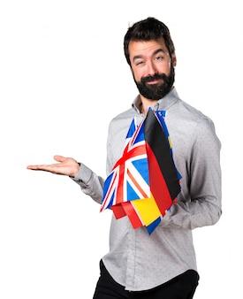 Hermoso hombre con barba sosteniendo muchas banderas y sosteniendo algo