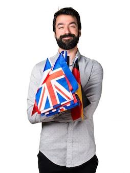 Hermoso hombre con barba sosteniendo muchas banderas