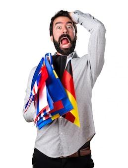 Hermoso hombre con barba sosteniendo muchas banderas y