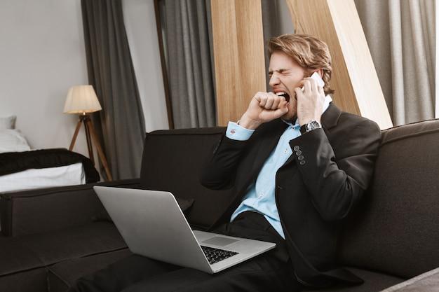 Hermoso hombre barbudo maduro en traje sentado en el dormitorio con la computadora portátil, aburrido por la noche hablar por teléfono con el jefe sobre el trabajo