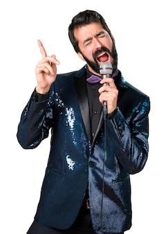 Hermoso hombre con chaqueta de lentejuelas cantando con micrófono