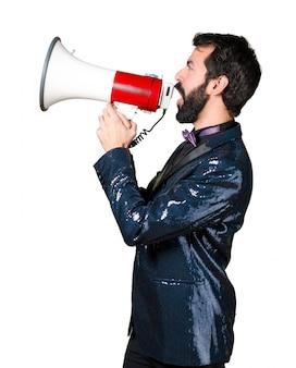 Hermoso hombre con chaqueta de lentejuelas gritando por megáfono