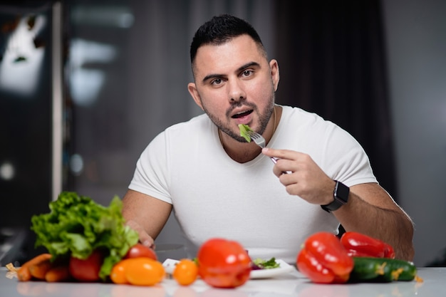 Hermoso hombre para comer comida vegetariana saludable en casa.