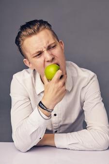 Hermoso hombre comiendo manzana, contra la superficie oscura