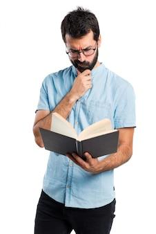 Hermoso hombre con gafas de lectura azul libro