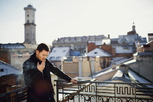 Hermoso hombre de pie en la terraza con hermosas vistas