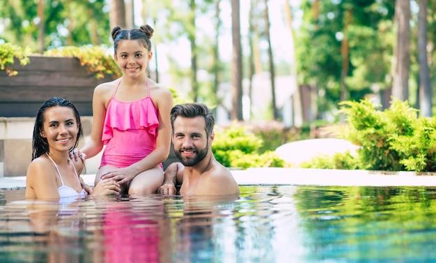 Hermoso hombre sonriente y linda mujer emocionada con su pequeña hija encantadora se divierten en la piscina de verano mientras descansan en el hotel.