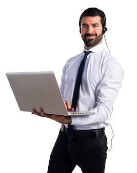 Hermoso hombre de telemarketer con ordenador portátil