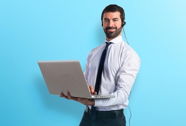 Hermoso hombre de telemarketer con portátil sobre fondo de colores