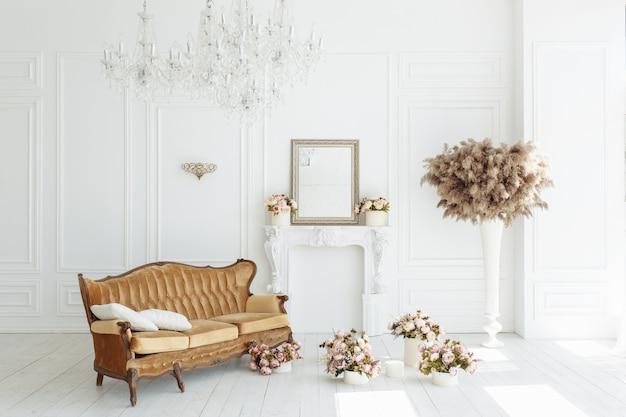 Hermoso interior blanco clásico con una chimenea, un sofá marrón y una lámpara de araña vintage.