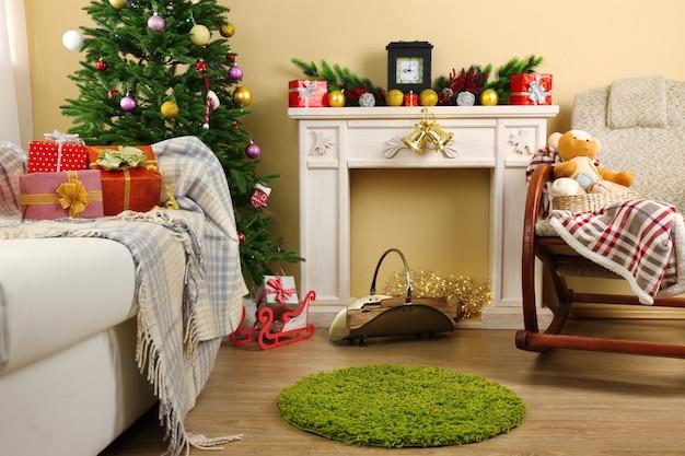 Hermoso interior de navidad con chimenea decorativa y abeto
