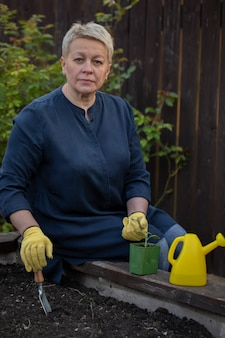 Hermoso jardinero replantando pimiento joven de maceta en cama de jardín elevada