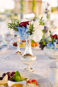 Hermoso jarrón de plata con un ramo de flores en la decoración de la mesa de la boda y la boda, cumpleaños, hogar