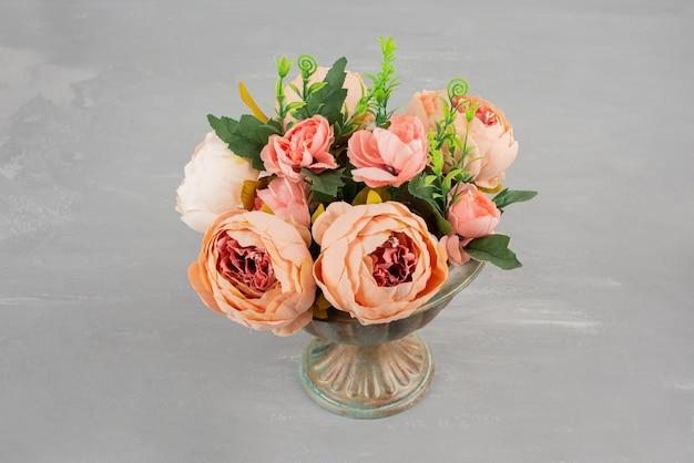 Hermoso jarrón de rosas rosadas en mesa gris.