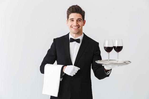 Hermoso joven camarero vistiendo esmoquin presentando una bandeja con dos copas de vino tinto aislado sobre pared gris