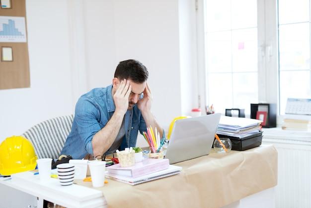 Hermoso joven diseñador moderno cansado haciendo un descanso del trabajo con masajear la cabeza y cerrar los ojos en la oficina brillante.