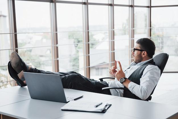 Hermoso joven empresario con gafas sosteniendo sus piernas sobre la mesa mirando una computadora portátil en la oficina