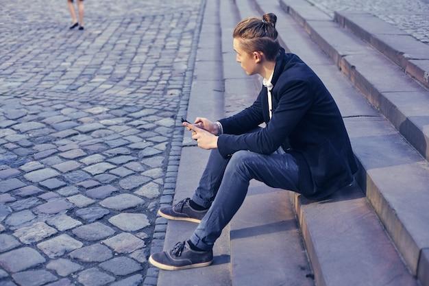 Hermoso joven empresario sentado en una escalera, comunicándose a través de un teléfono