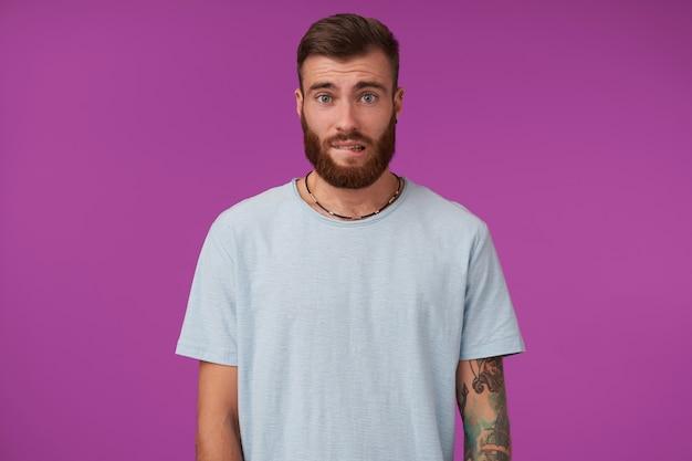 Hermoso joven morena tatuada con barba que parece culpable y se muerde el labio inferior, manteniendo las manos hacia abajo mientras posa en púrpura en ropa casual