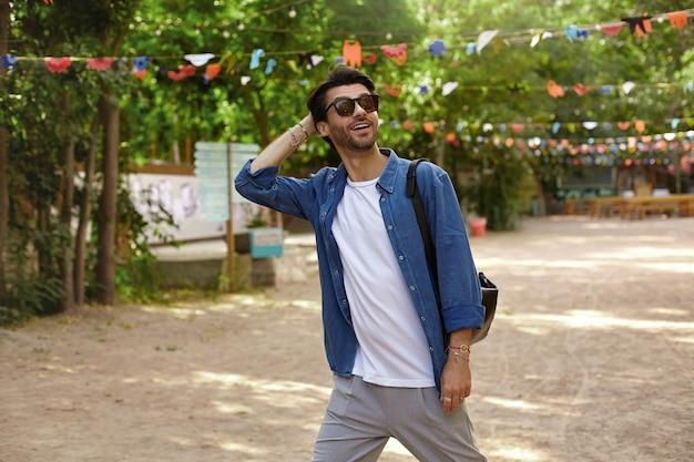 Hermoso joven de pelo oscuro con gafas de sol caminando por el parque de la ciudad, mirando hacia arriba con una amplia sonrisa y manteniendo la mano en la parte posterior de la cabeza