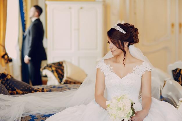 Un hermoso joven vistiendo un traje negro de pie junto a su novia
