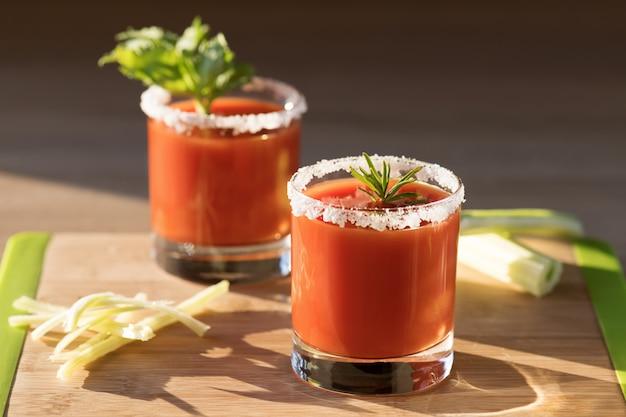 Hermoso jugo de tomate en vasos con apio, sal y romero en una tabla para cortar madera en un día soleado