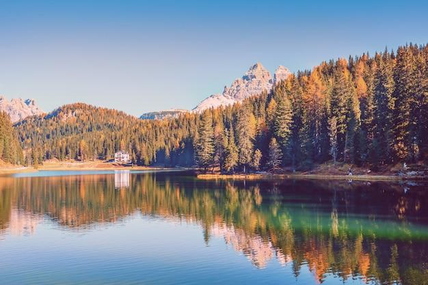 Hermoso lago con montañas y árboles de otoño reflejo en el agua