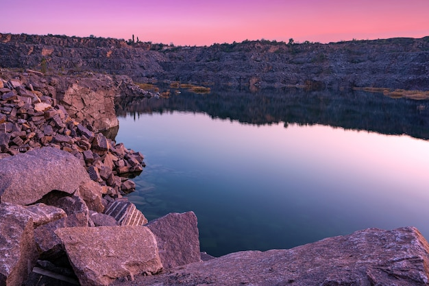 Un hermoso lago muy pequeño rodeado por grandes montones de desechos de piedra del trabajo duro en la mina