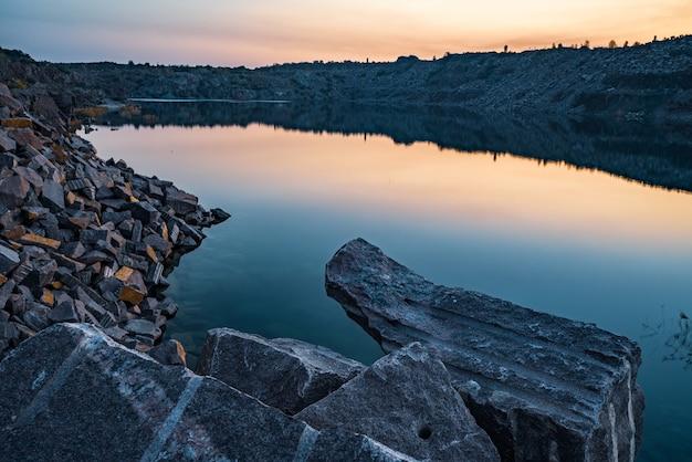 Hermoso lago rodeado por grandes montones de desechos de piedra del trabajo duro en una mina contra un hermoso cielo nocturno con estrellas