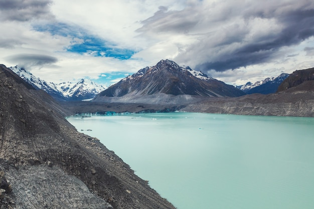 Hermoso lago turquesa del glaciar tasman y montañas rocosas en las nubes, el parque nacional mount cook, isla sur, nueva zelanda