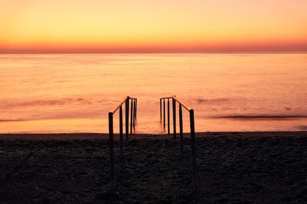 Hermoso mar cálido y escaleras en la playa para entrar al agua