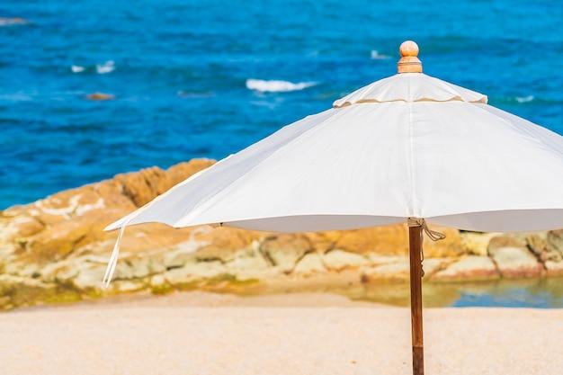 Hermoso mar de playa tropical con sombrilla y silla alrededor de nubes blancas y cielo azul para viajes de vacaciones