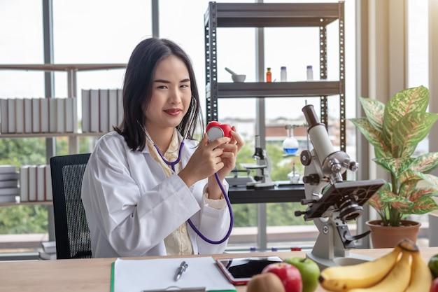 Hermoso médico asiático que muestra un examen de corazón rojo en el escritorio de la oficina en una oficina moderna