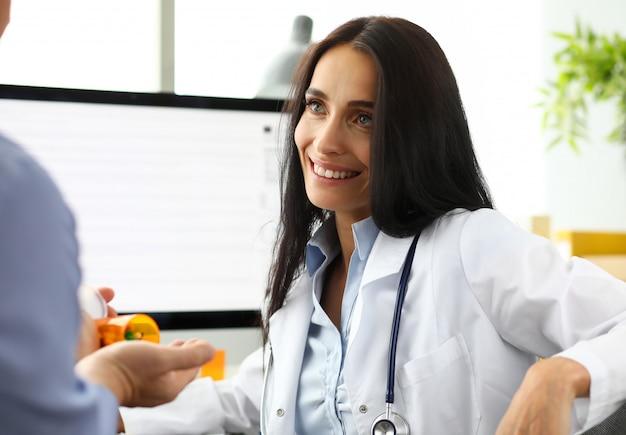Hermoso médico de raza caucásica hablando con un visitante masculino dándole prescripción