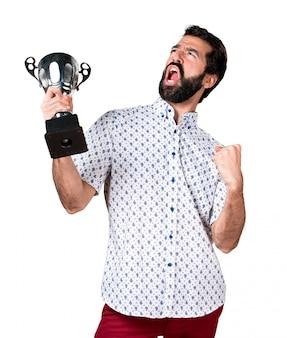 Hermoso morena hombre con barba sosteniendo un trofeo