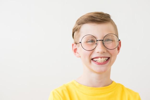 Hermoso muchacho adolescente riendo con gafas grandes y camiseta amarilla