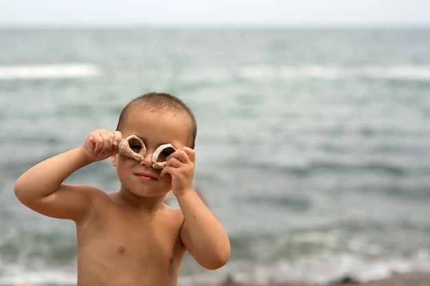 Hermoso niño atractivo posando en la cámara sosteniendo dos conchas alrededor de los ojos.