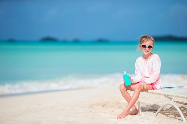 Hermoso niño con botella de crema solar en playa tropical